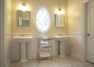 eliptical window and white pedestal sinks